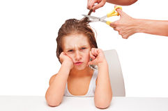 Sad boy haircut. Sad kid boy getting haircut at home royalty free stock images