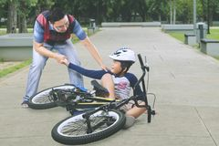 Sad boy helped by his father after falling from a bike stock photos
