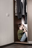 Sad boy, hiding in the closet. At home stock image