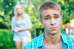 Sad boy with his girlfriend on the background. At the park Royalty Free Stock Image