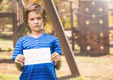 Sad boy holding help sign against playground Royalty Free Stock Photo
