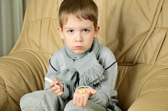 Sad boy holding a thermometer and pills horizontal Royalty Free Stock Photography