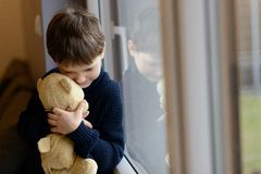 Sad boy is hugging his teddy bear. Royalty Free Stock Photo