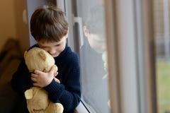 Sad boy is hugging his teddy bear. Royalty Free Stock Photo
