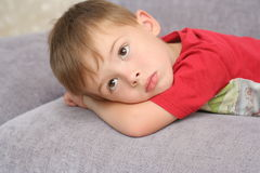 The sad boy lays on a sofa Royalty Free Stock Photos