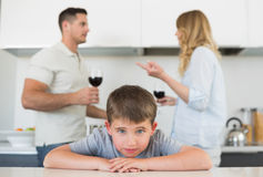 Sad boy leaning on table while parents arguing Stock Photos