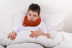 Sad boy lies on the bed, neck is rewound with a warm scarf stock photos