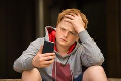 Free Sad Boy Looking At Mobile Phone Royalty Free Stock Image - 86380506
