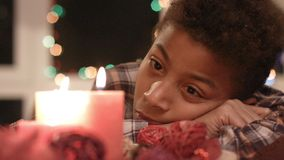 Sad boy looking at candle. stock footage