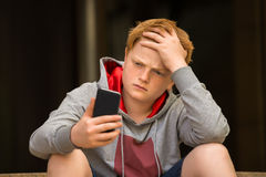 Sad Boy Looking At Mobile Phone. With Hand On Head royalty free stock image