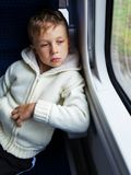 Boy looking out train window. Sad boy looking out the window of the departing train Royalty Free Stock Photos