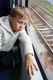 Boy looking out train window. Sad boy looking out the window of the departing train Stock Images