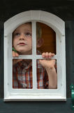 Sad boy looking  through the window. Sad boy looks thoughtfully through the window  he wants to play outside Royalty Free Stock Photo
