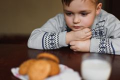 Sad boy looks at cookies and milk. royalty free stock image