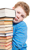 Sad boy looks out from behind a pile of books Stock Photos
