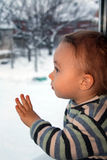 Sad boy looks thoughtfully through the window. For window winter. Much coldly. The Small boy sits on windowsill and looks through window Royalty Free Stock Photos