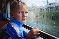 SAD BOY LOOKS IN WINDOW. Sad boy looks thoughtfully through the wet window of the train Royalty Free Stock Images