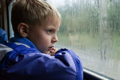 SAD BOY LOOKS IN WINDOW. Sad boy looks thoughtfully through the wet window of the train Royalty Free Stock Image