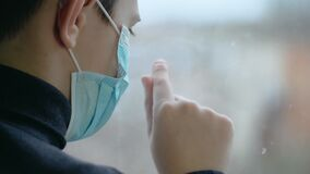 Sad boy in medical mask draws finger on window out of boredom during world corona virus pandemic