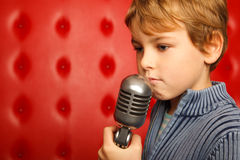 Sad boy with microphone on rack against red wall Stock Images