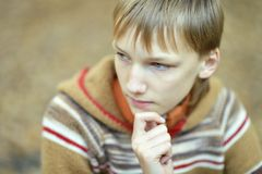 Sad boy in nature. Portrait of a sad little boy outdoors in autumn royalty free stock photography