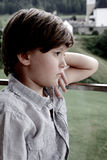 Sad boy pensive in front of mountains closeup Royalty Free Stock Image