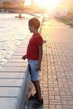 Sad boy portrait on embankment backlit, toned image Royalty Free Stock Photo