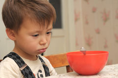 Sad boy refusing to eat. Four year old boy refusing to eat his dinner stock photography