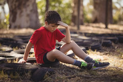 Sad boy relaxing on tyre during obstacle course. In boot campboot, camp, boot camp, sunny, summer, park, kid, sportswear, athlete, athletic, obstacle course Royalty Free Stock Photo