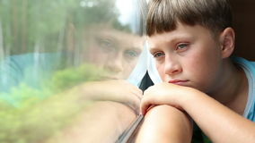 Sad boy rides in a train. He sits in the coupe and looks out the window stock video footage