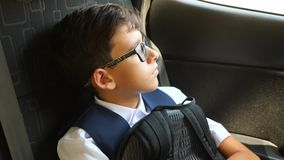 The sad boy is riding in the car in school uniform. 4k, slow-motion stock video footage