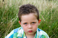 Sad boy scowling whilst looking ahead Royalty Free Stock Photography