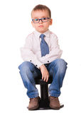 Sad boy in shirt and jeans. Small sad boy in glasses, shirt and jeans sitting on the black chair. Isolated on white background Stock Photography