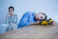 Sad boy sick of autism. Plays with yellow toy car while his mother is looking at him Royalty Free Stock Photography
