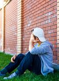 Sad Boy outdoor. Sad Boy sit by the Brick Wall outdoor Stock Images