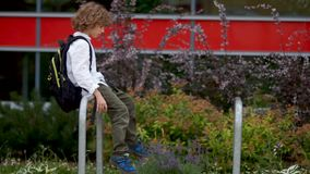 A sad boy sits on the railing in the courtyard near the school. The schoolboy gets up and goes sadly. Psychological. Problems of adolescence stock footage