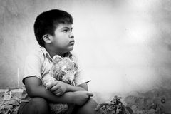 Sad boy sitting alone with old teddy bear Royalty Free Stock Images