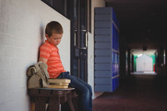 Sad boy sitting on bench by wall in corridor. At school Stock Photo