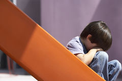Sad boy (4-6) sitting at bottom of orange slide in playground, head in hands, crying, profile Royalty Free Stock Photos