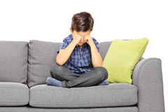 Sad boy sitting on a couch and crying Stock Image
