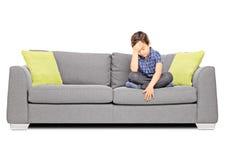 Sad boy sitting on a couch Stock Photos