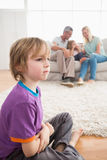 Sad boy sitting on floor while parents enjoying with sister Stock Images