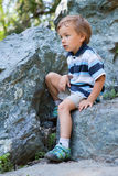 Sad boy sitting on rock. Royalty Free Stock Photography