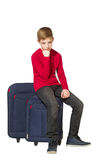 Sad boy sitting on travel bags isolated on white Stock Photography