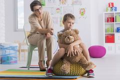 Sad boy hugs teddy bear. Sad boy sitting on yellow pouf being turned back to the psychotherapist and hugs teddy bear Stock Photos