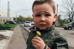 Sad boy sniffs dandelion, spring. children`s psychological trauma. unhappy child royalty free stock photos