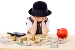 Sad boy at the table with money Royalty Free Stock Photography