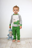 Sad boy with toy. Sad toddler boy in his pajamas and bare feet, holding his stuffed animal security toy Stock Photos