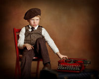 Sad boy with typewriter in chair Royalty Free Stock Images