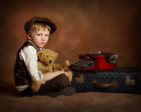 Sad boy typing with bear. Sad boy with teddy bear typing Royalty Free Stock Images
